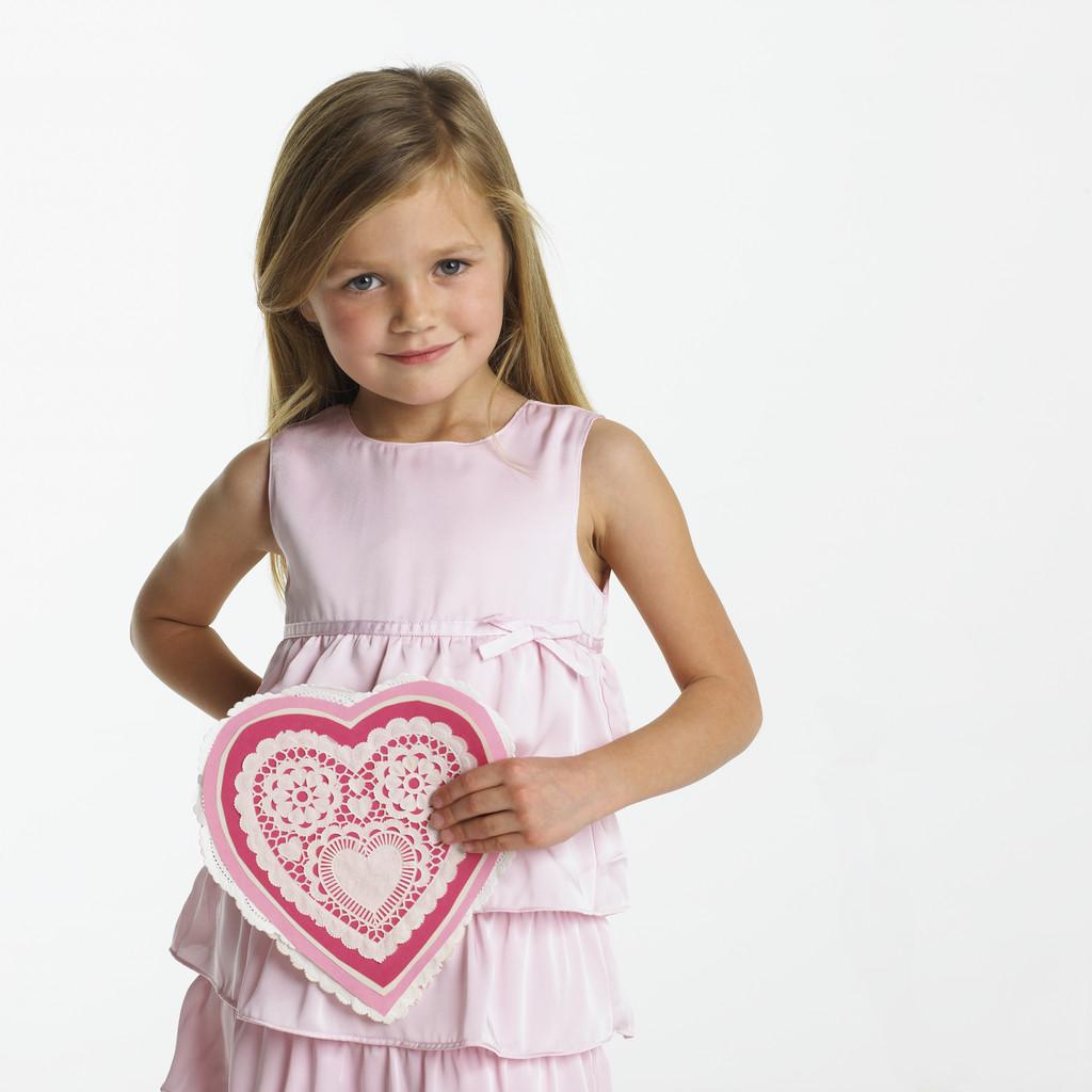 little girl in pink dress holding decorative valentine heart